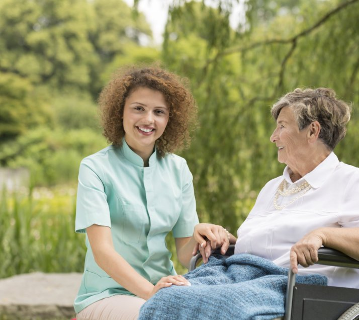caregiver and her old woman patient sitting