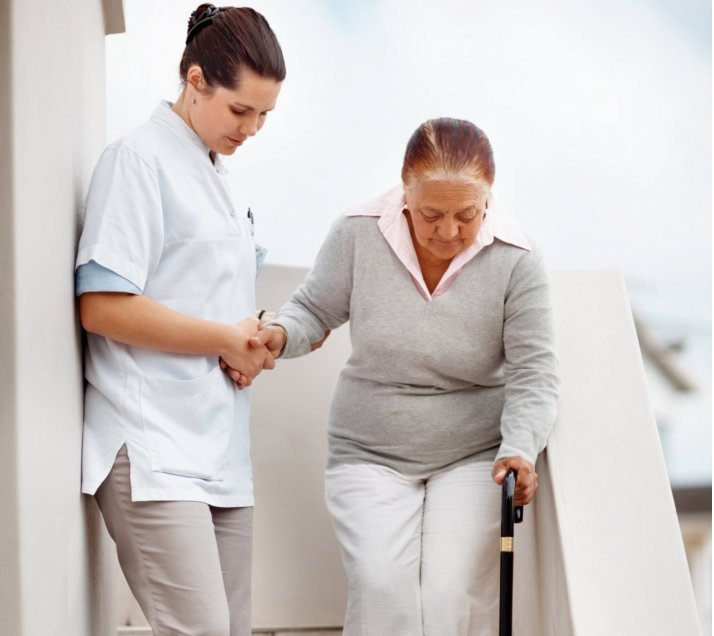 caregiver assisting her old patient in stairs