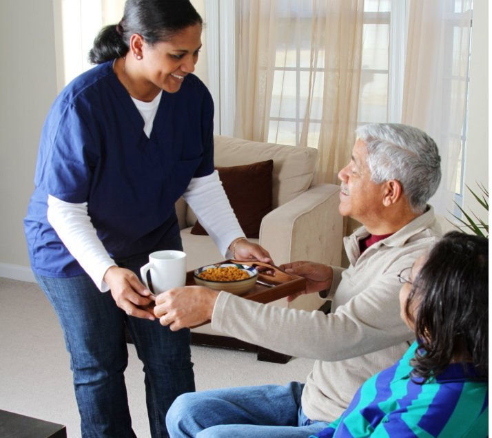 caregiver giving food to her one old patient